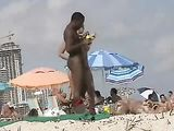 Naked black man with white women at the beach
